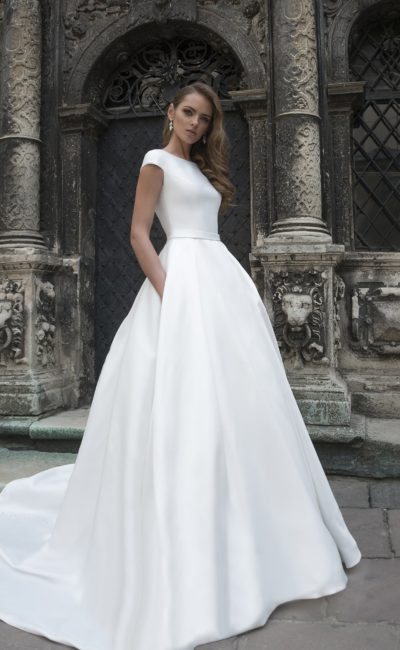 Лаконичное свадебное платье с вырезом под горло и карманами на пышной юбке.