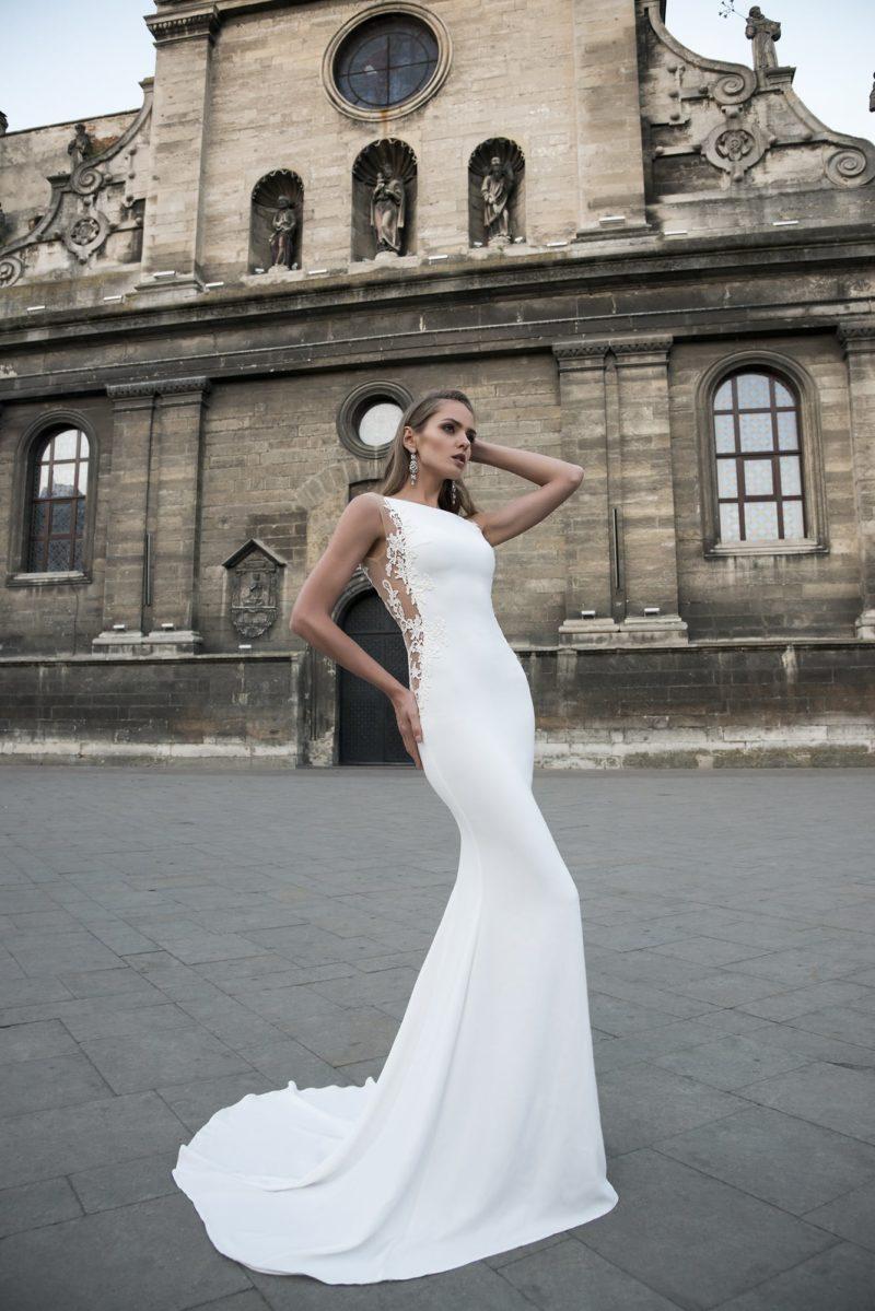 Облегающее фигуру свадебное платье с длинным шлейфом и тонкими вставками.