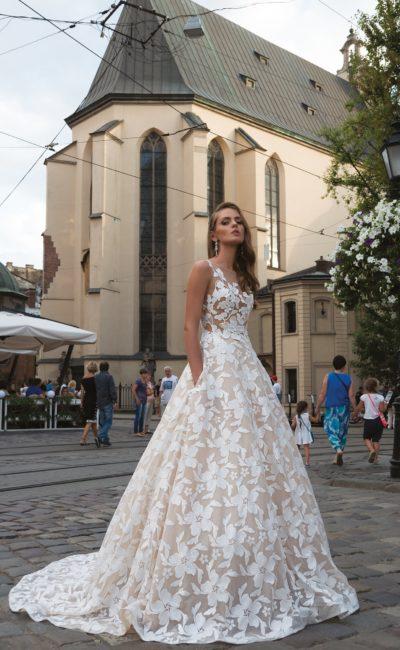 Бежевое свадебное платье пышного кроя с эффектной отделкой крупными белыми цветами.