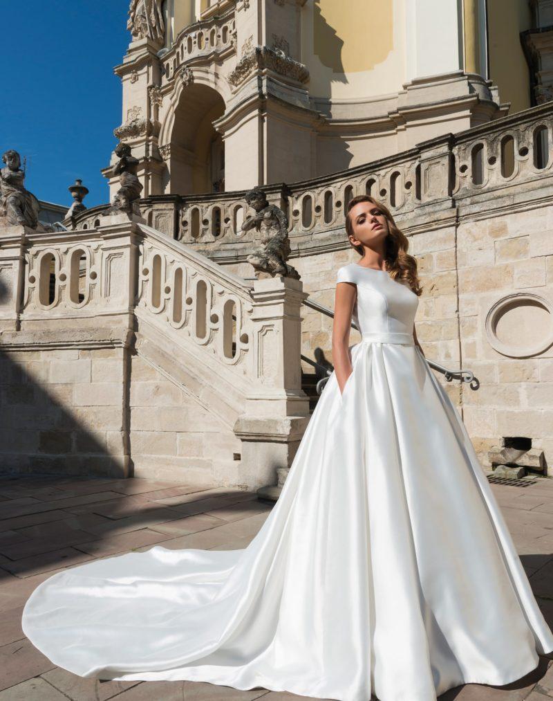 Атласное свадебное платье со скрытыми карманами и глубоким декольте на спинке.
