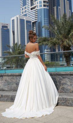 Пышное свадебное платье с атласной юбкой со шлейфом, открывающее плечи вырезом.