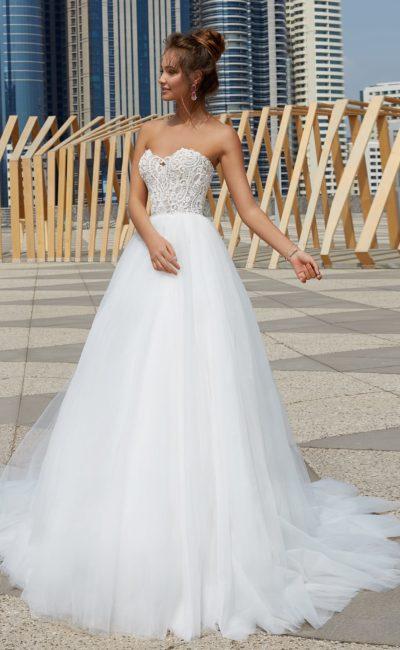 Пышное свадебное платье с романтичным фактурным верхом и многослойным подолом.