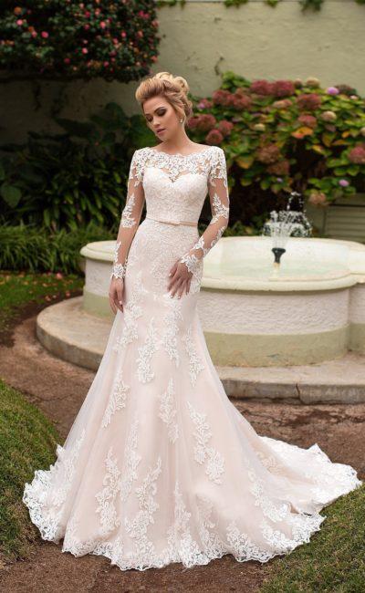 Облегающее свадебное платье с подкладкой цвета слоновой кости и длинным кружевным рукавом.