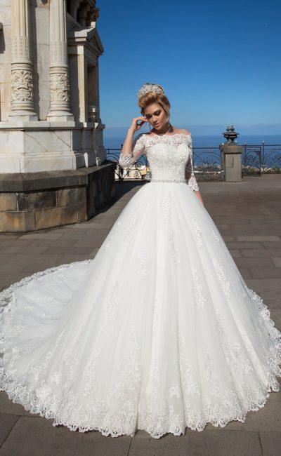Эффектное свадебное платье пышного силуэта с кружевным портретным декольте и рукавом.