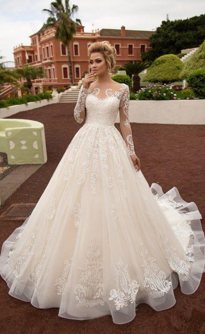 Кремовое свадебное платье великолепного А-силуэта с длинным рукавом и эффектным шлейфом.