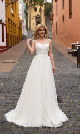 Необычное свадебное платье с многослойной юбкой и отделкой верха тонкой тканью.