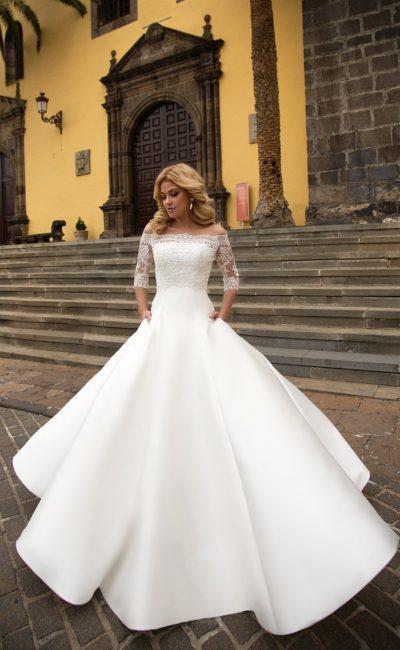 Впечатляющее свадебное платье с атласной юбкой и кружевным верхом с рукавом.