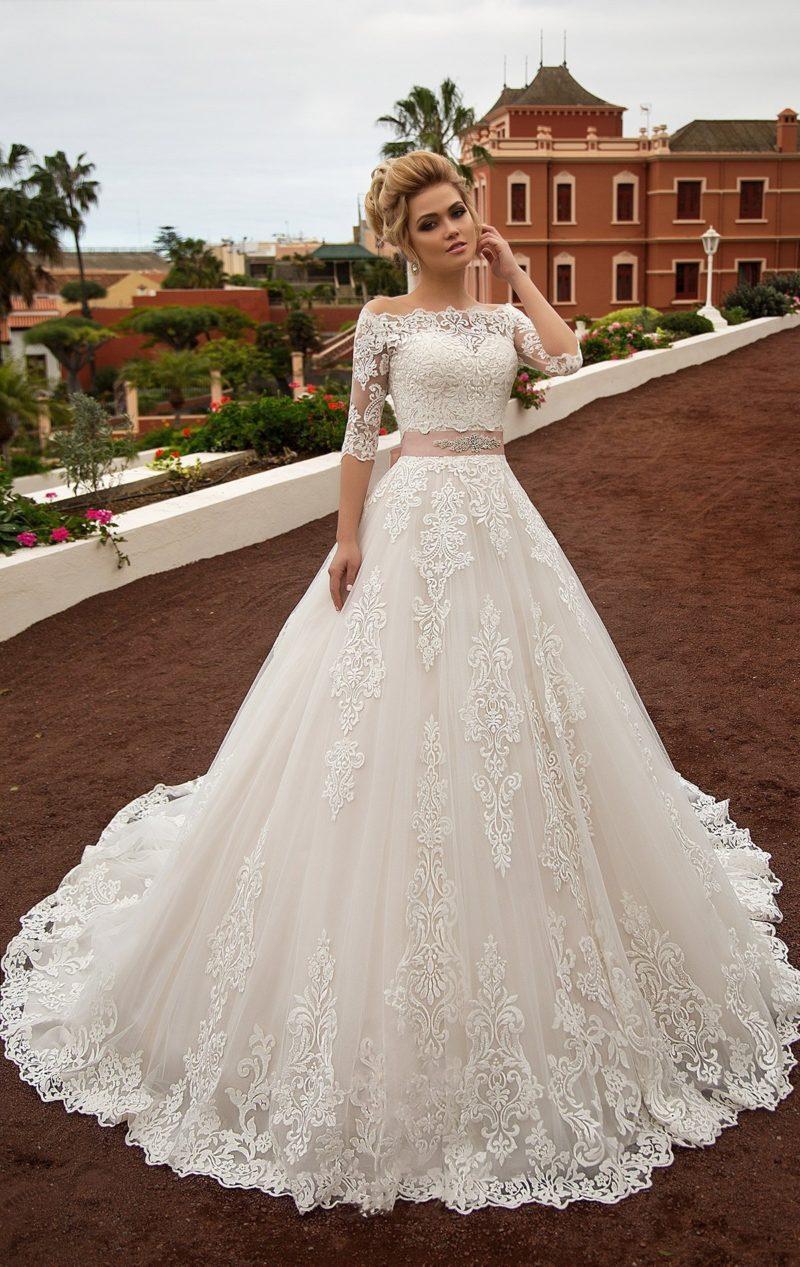Свадебное платье «принцесса» цвета слоновой кости с широким розовым поясом на талии.