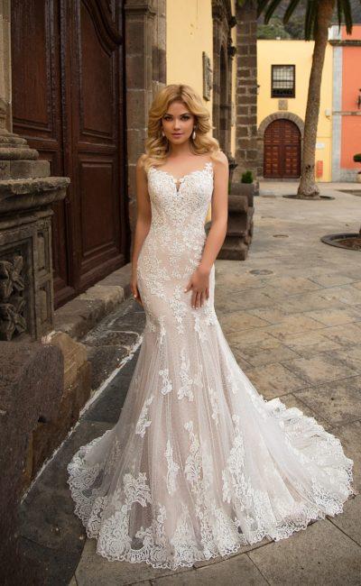 Облегающее свадебное платье на бежевой подкладке, дополненное верхней юбкой.