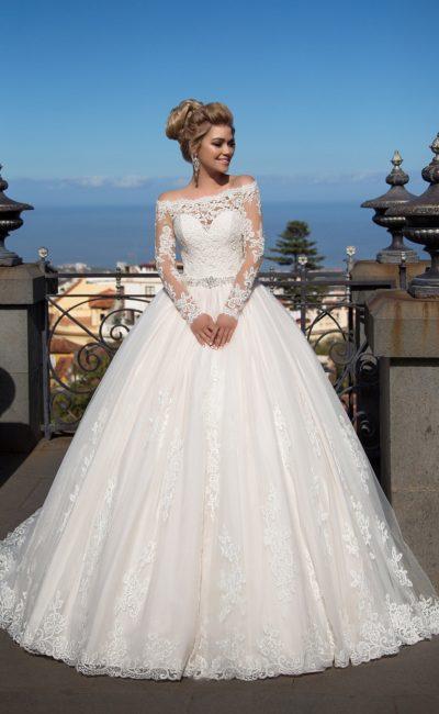 Роскошное свадебное платье пышного силуэта с портретным вырезом и длинным рукавом.