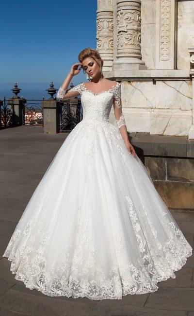 Кружевное свадебное платье с пышным подолом и облегающими полупрозрачными рукавами.