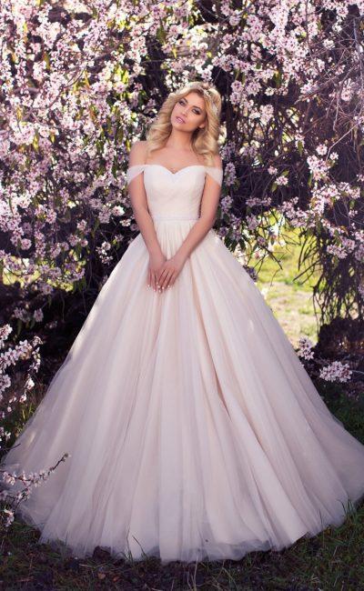 Свадебное платье кремового оттенка с изящным открытым декольте с бретелями на предплечьях.