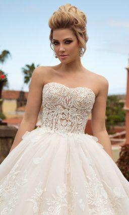 Кремовое свадебное платье с объемным декором пышной юбки и кружевным верхом.