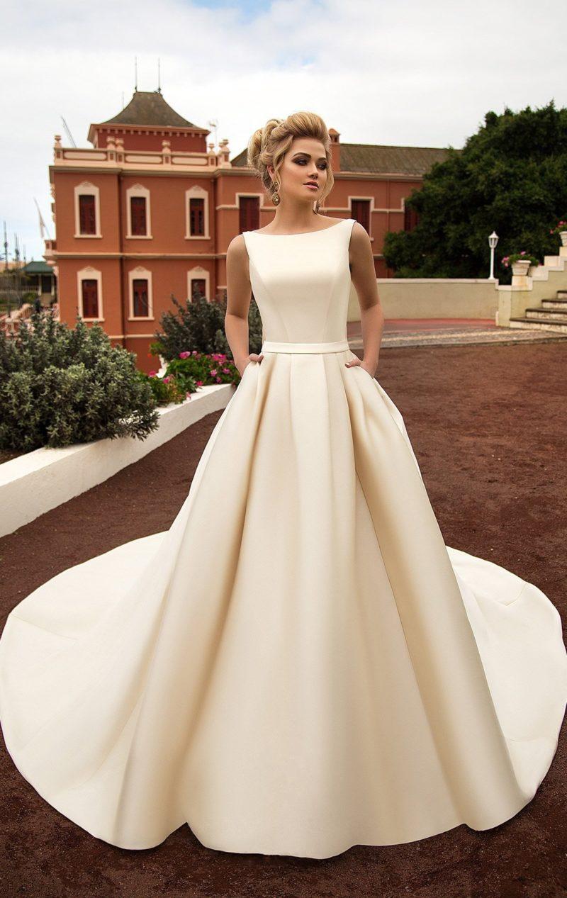 Золотистое свадебное платье пышного кроя с элегантным закрытым лифом и узким поясом.