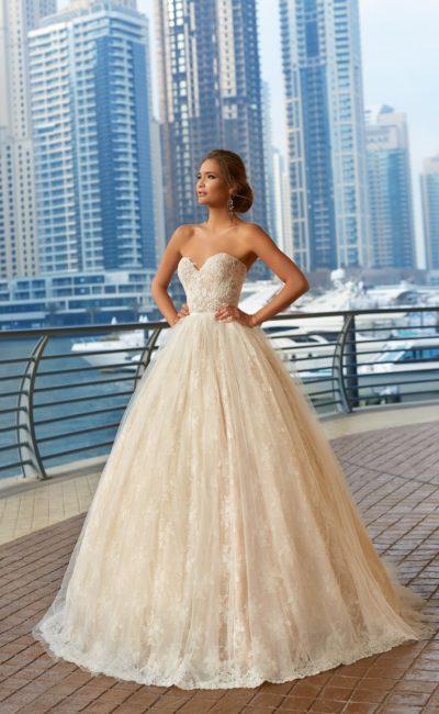 Бежевое свадебное платье с лифом в форме сердца и роскошной многослойной юбкой.