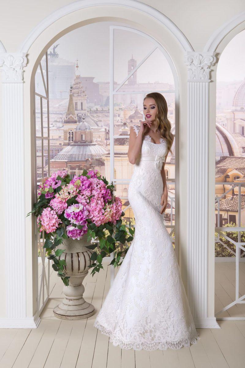 Кружевное свадебное платье облегающего кроя с узким поясом, украшенным бантом.