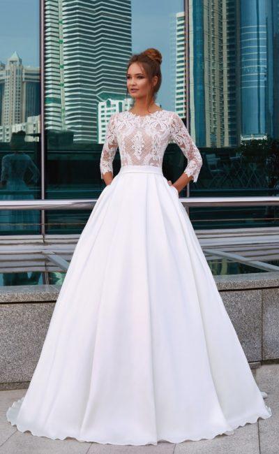 Роскошное свадебное платье с кружевным верхом на бежевой подкладке и карманами в подоле.