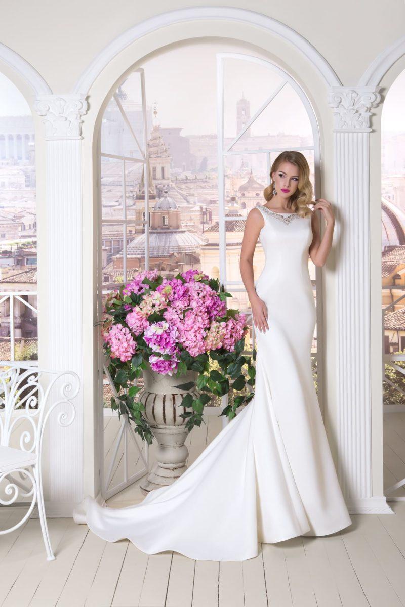 Прямое свадебное платье с вырезом лодочкой и торжественным длинным шлейфом.