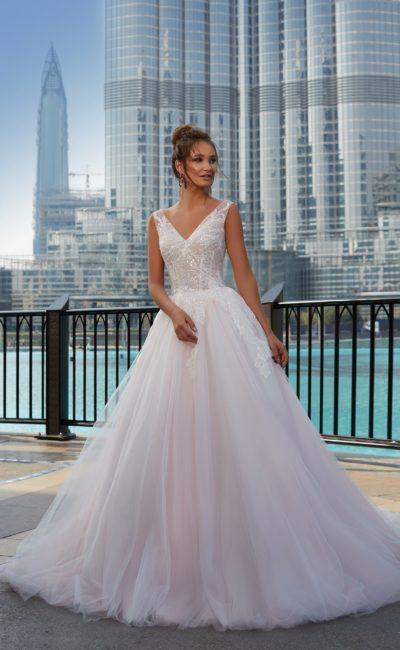 Розовое свадебное платье с пышным силуэтом и V-образными вырезами на лифе и спинке.