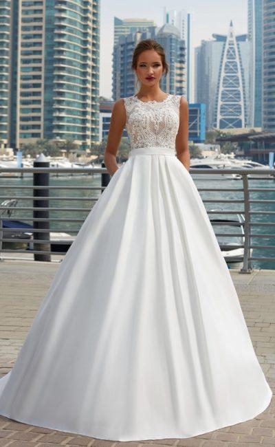 Изысканное свадебное платье с закрытым ажурным верхом и юбкой со скрытыми карманами.
