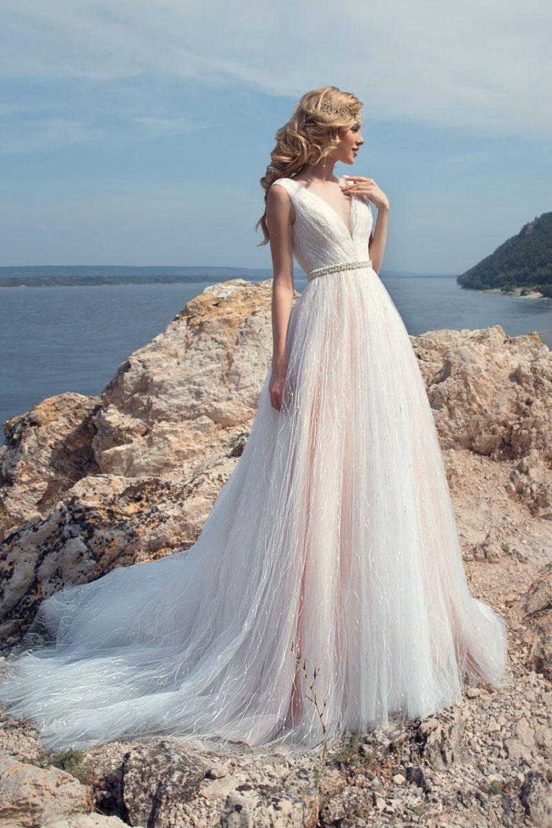 Пляжное свадебное платье кремового цвета с юбкой А-силуэта и V-образным вырезом.
