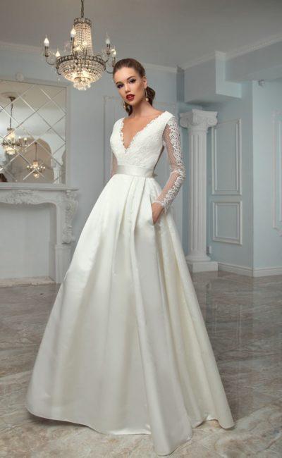 Атласное свадебное платье с длинным полупрозрачным рукавом и V-образным вырезом.