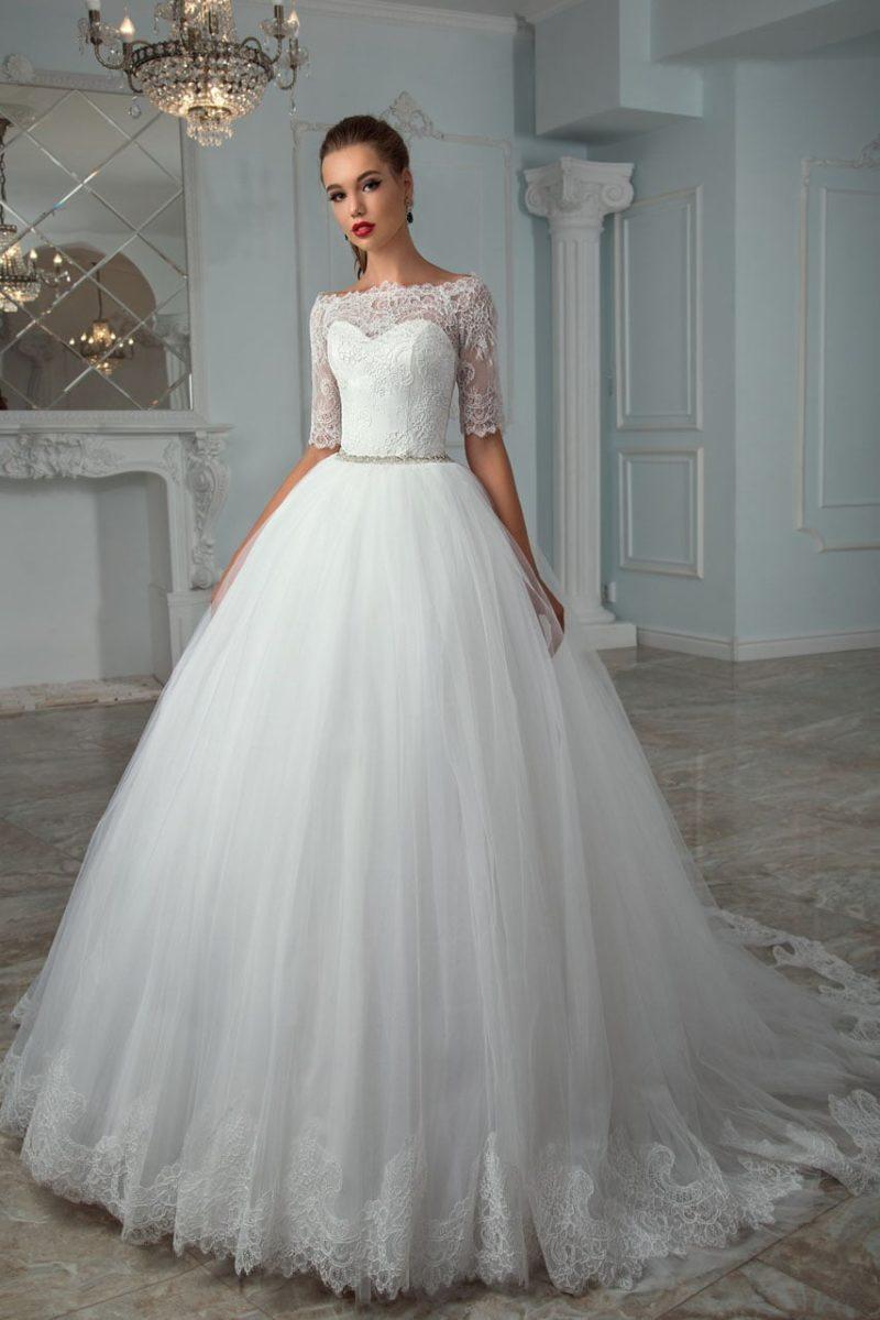 Пышное свадебное платье с портретным декольте и узким бисерным поясом на талии.