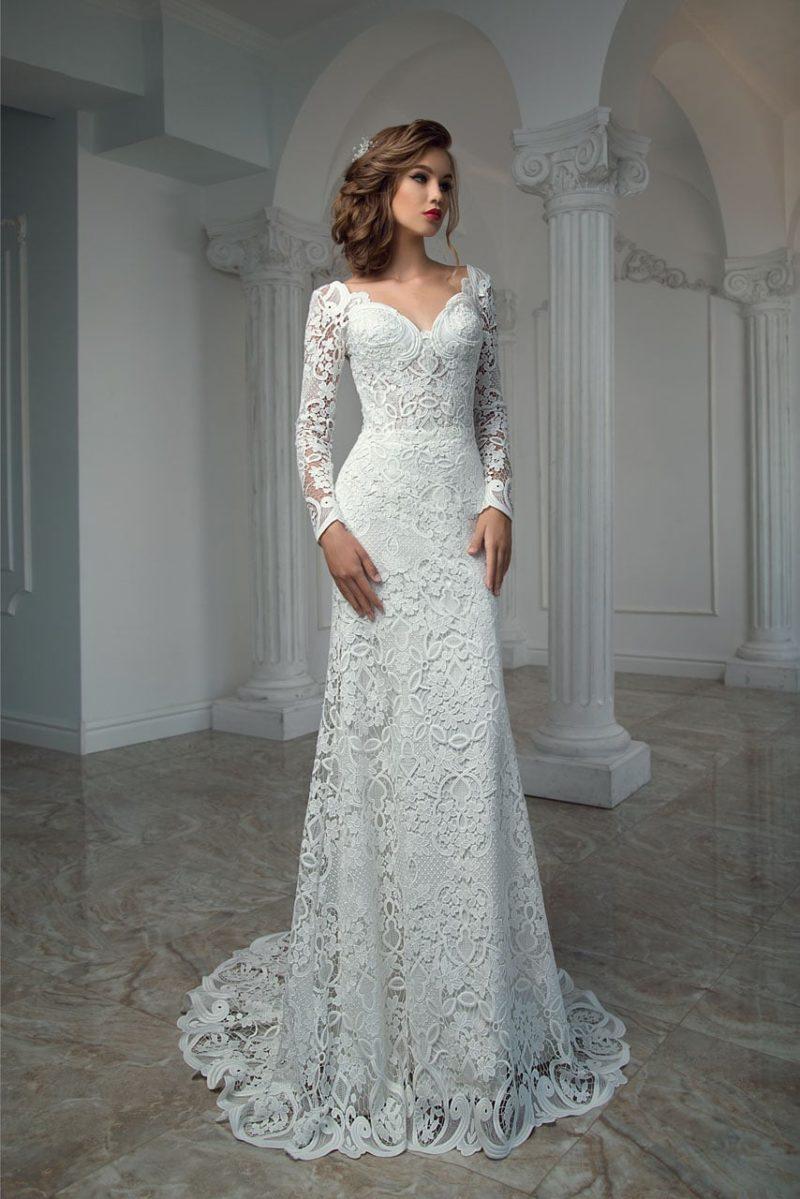 Прямое свадебное платье с глубоким декольте и длинным рукавом из плотного кружева.