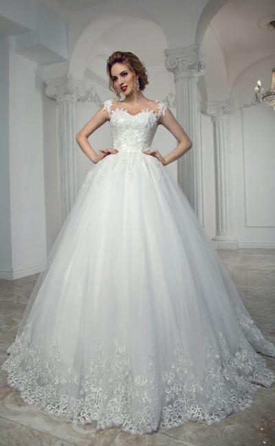 Кружевное свадебное платье пышного кроя с открытым декольте и фигурными бретелями.