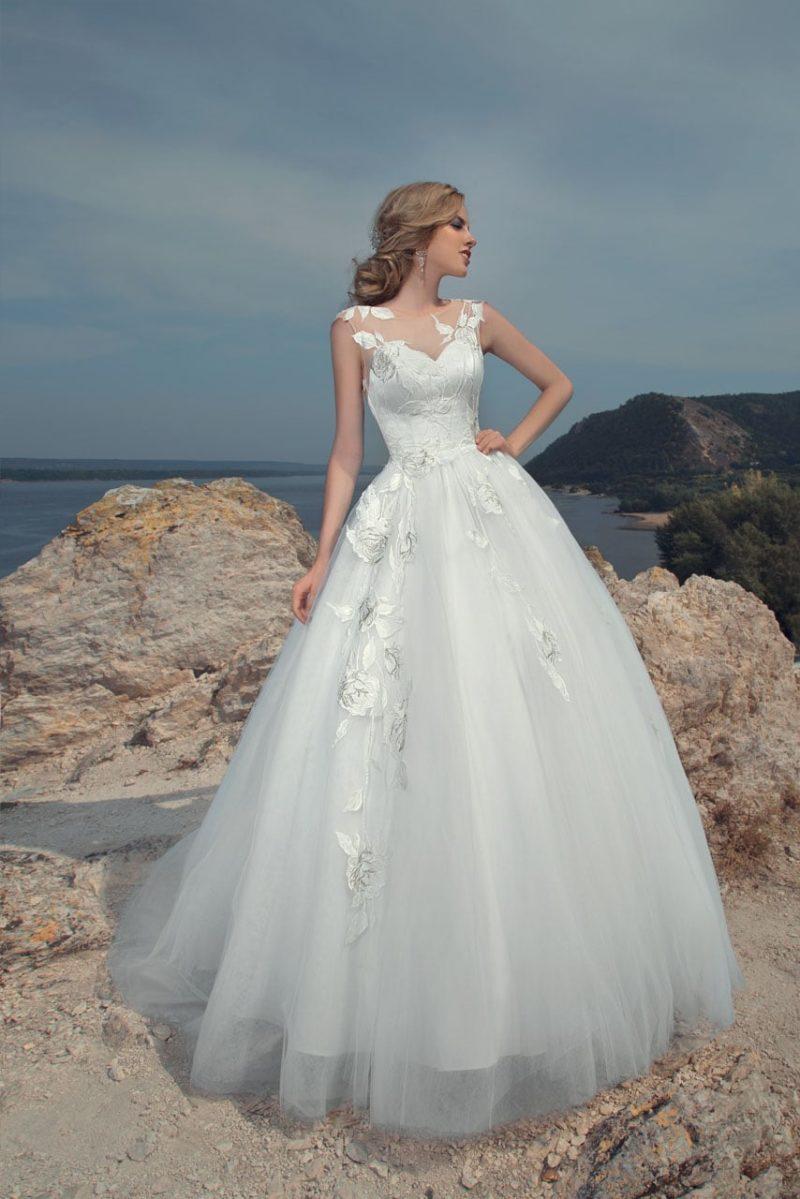 Пляжное свадебное платье пышного кроя, декорированное глянцевыми аппликациями.