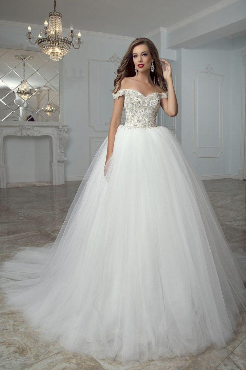 Пышное свадебное платье с открытым вырезом и бретелями на предплечьях.
