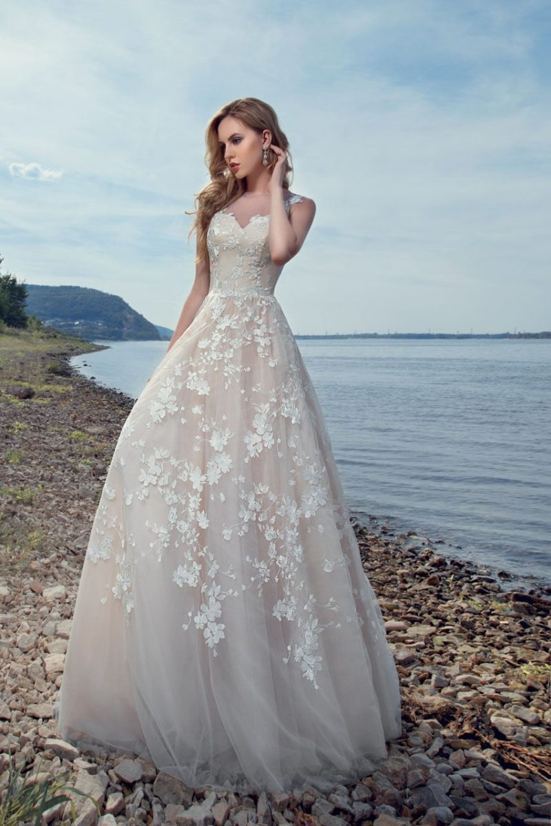 Пляжное свадебное платье бежевого цвета с романтичным декором аппликациями.