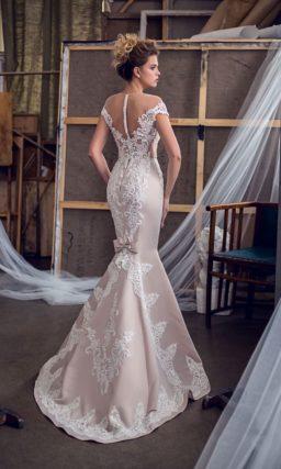 Нежное свадебное платье розового цвета с кружевной отделкой и бантом сзади на юбке.
