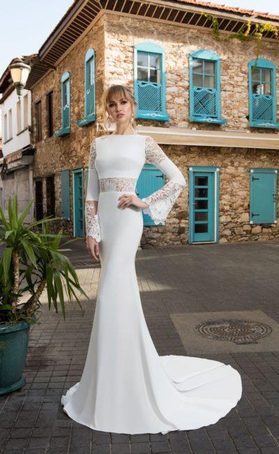 Драматичное свадебное платье облегающего кроя с ажурным рукавом и вставкой на талии.