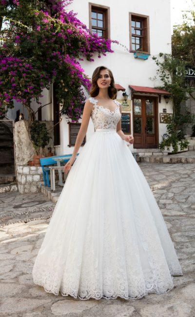 Пышное свадебное платье с элегантным поясом и крупным кружевным декором по верху.