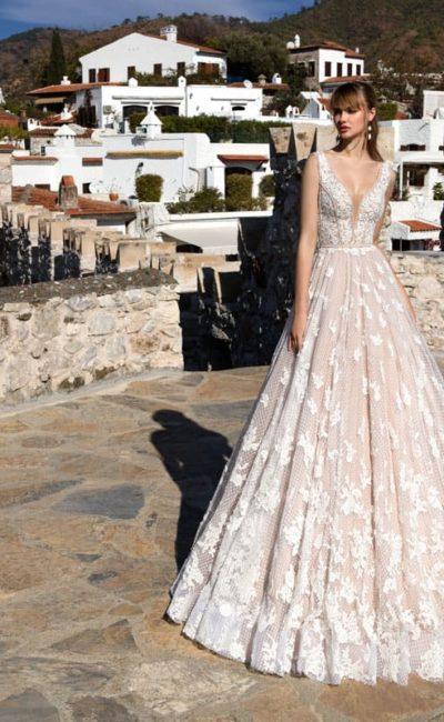 Бежевое свадебное платье с отделкой белым кружевом и стильным V-образным декольте.
