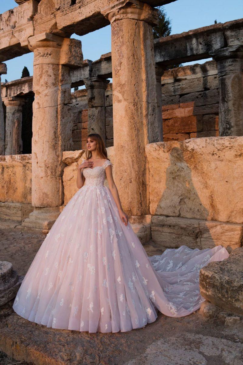 Розовое свадебное платье пышного кроя с эффектным шлейфом и кружевным декором.