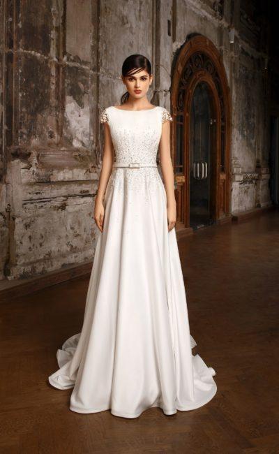 Закрытое свадебное платье с вырезом бато, коротким рукавом и женственной юбкой.