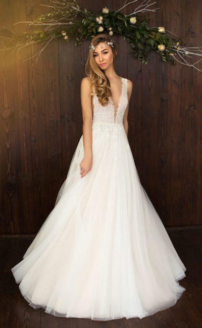 Потрясающее свадебное платье с глубоким декольте, обрамленным кружевными бретелями.