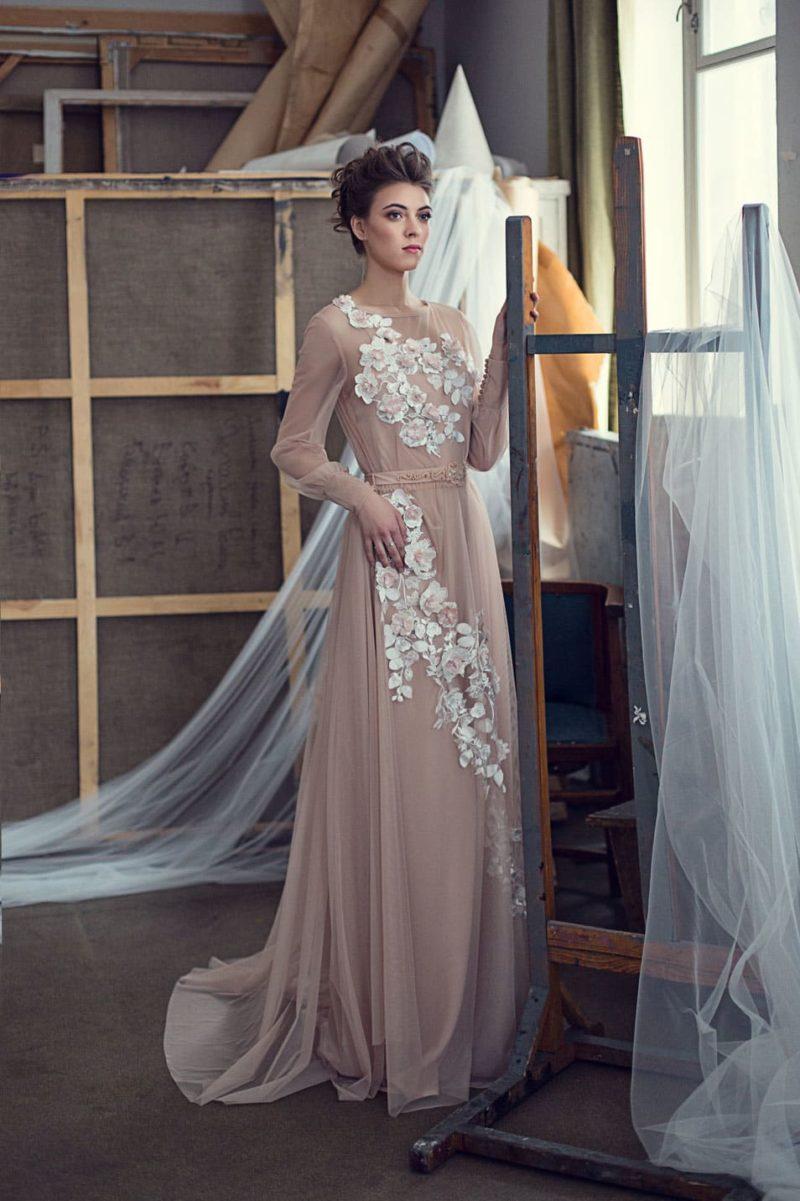 Бежевое свадебное платье прямого кроя с длинным рукавом и объемным белым декором.