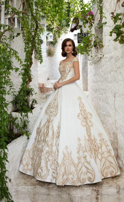 Оригинальное свадебное платье с пышной юбкой, оформленное золотистой вышивкой.