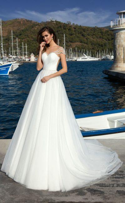 Лаконичное свадебное платье с полупрозрачной спинкой и воздушным низом со шлейфом.