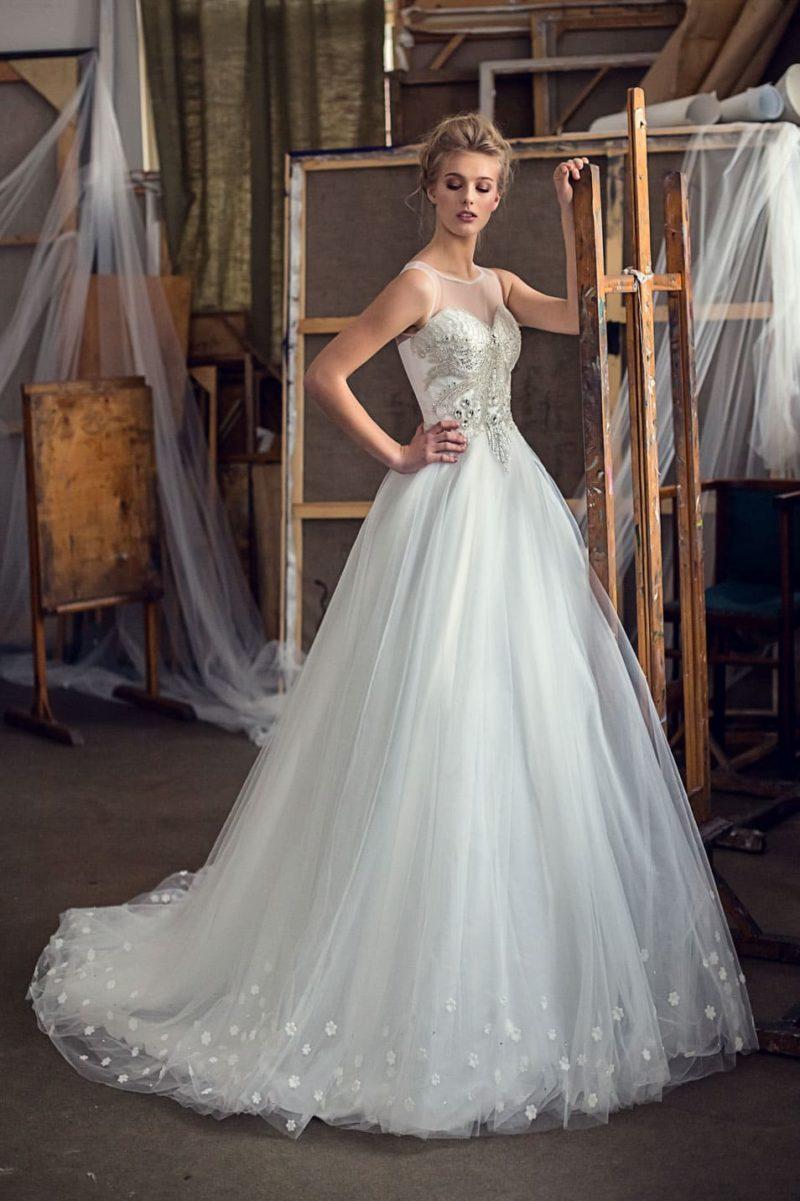 Пышное свадебное платье с многослойной юбкой и сверкающим декором закрытого верха.