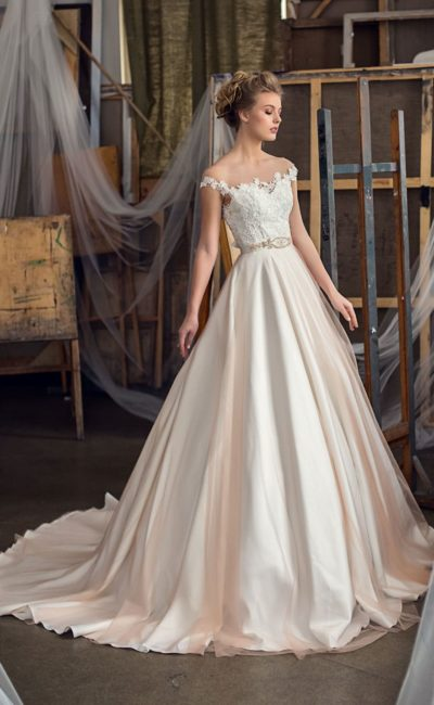 Кремовое свадебное платье из атласа с юбкой А-силуэта и кружевным верхом с бретелями.