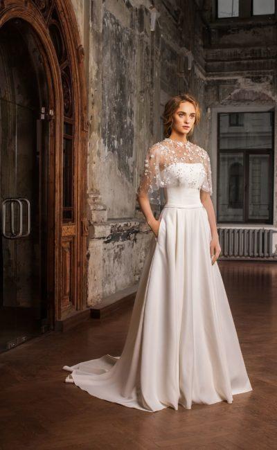 Атласное свадебное платье А-силуэта с изящным поясом и тонкой кружевной накидкой.