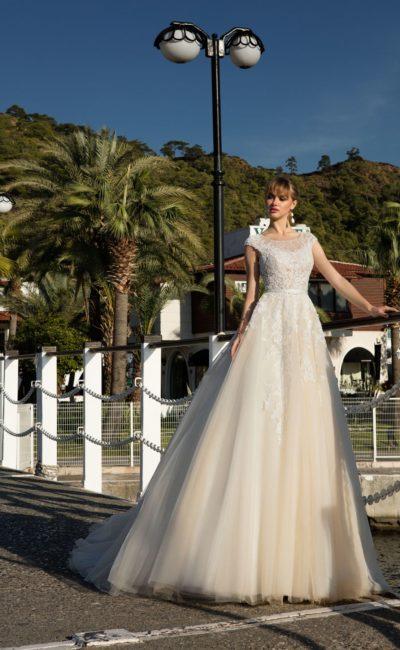 Пышное свадебное платье кремового оттенка с коротким рукавом и изящным вырезом.