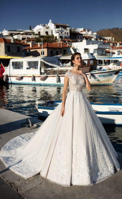 Свадебное платье с полупрозрачным закрытым верхом и длинным полукругом шлейфа.