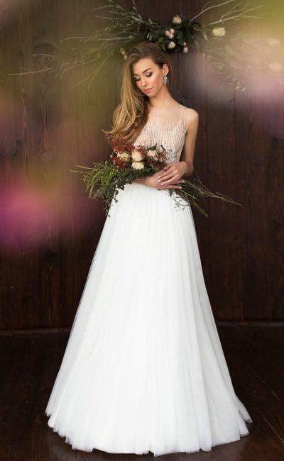 Элегантное свадебное платье с полупрозрачным верхом и воздушной юбкой А-силуэта.