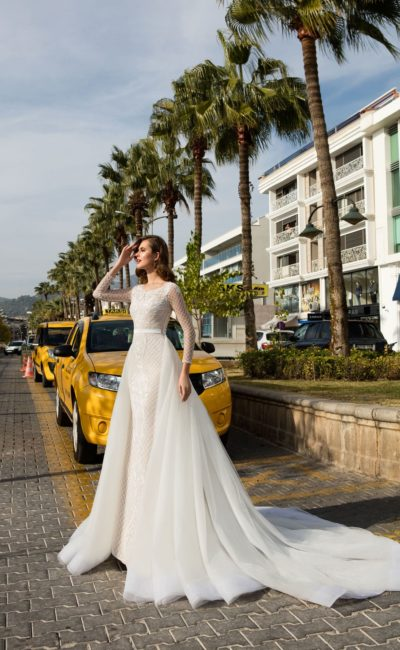Эффектное свадебное платье с длинным рукавом и объемной верхней юбкой.
