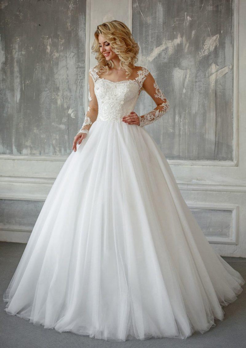Пышное свадебное платье с классической кружевной отделкой верха и длинным рукавом.